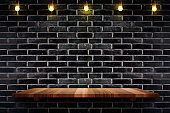 Empty brown plank wood shelf at black brick wall background with light bulbs string,Mockup for display or montage of product or design.