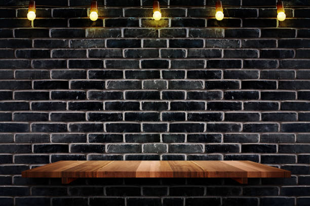 Empty brown plank wood shelf at black brick wall background with light bulbs string,Mockup for display or montage of product or design. stock photo