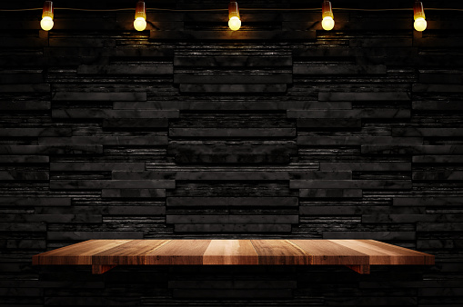 istock Empty brown plank wood shelf at black layer marble tile wall background,Mock up for display or montage of product or design 1047533606