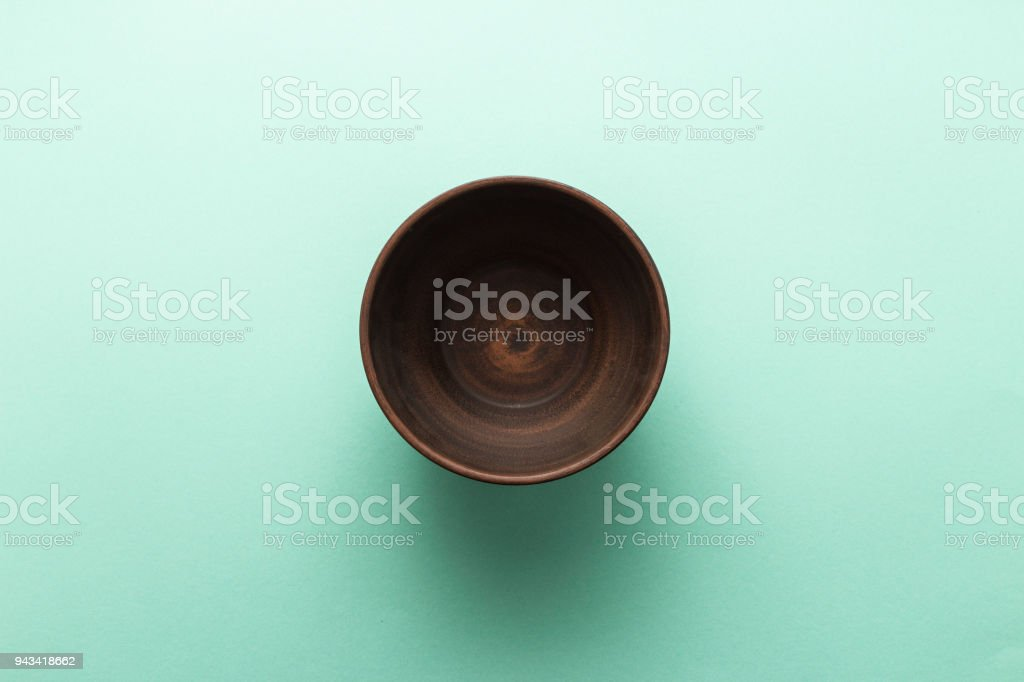 Empty brown plate on pastel green background, top view, flat lay stock photo