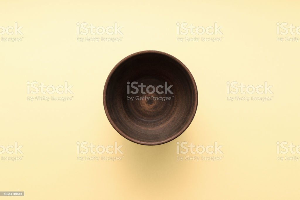 Empty brown plate on pastel yellow background, top view, flat lay stock photo