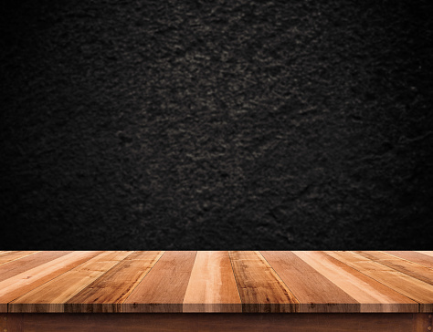 istock Empty brown wood table top with blurred balck rough stone 593305530