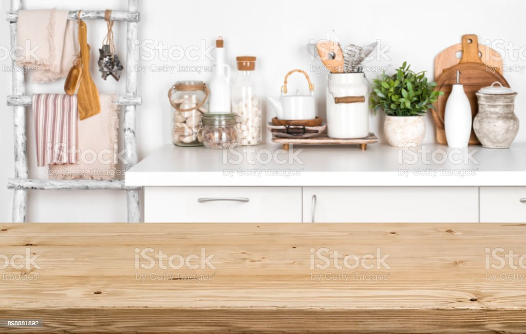 Empty brown wooden table with blurred image of kitchen interior stock photo