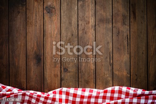 Backgrounds: high angle view of an empty brown wooden table with vertical stripes. A crumpled red and white gingham tablecloth is at the edge of the bottom border of an horizontal frame leaving a useful copy space for text, logo or product montage. Predominant colors are brown and red. Low key DSRL indoors photo taken with Canon EOS 5D Mk II and Canon EF 24-105mm f/4L IS USM Wide Angle Zoom Lens