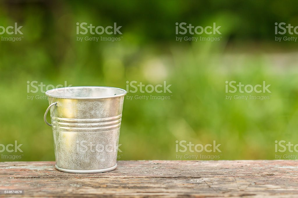 empty bucket on the board on a background of green стоковое фото