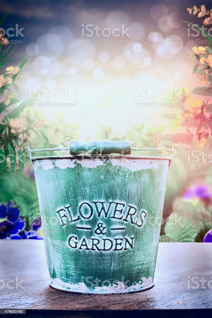 Empty bucket on wooden table over flowers bed background stock photo