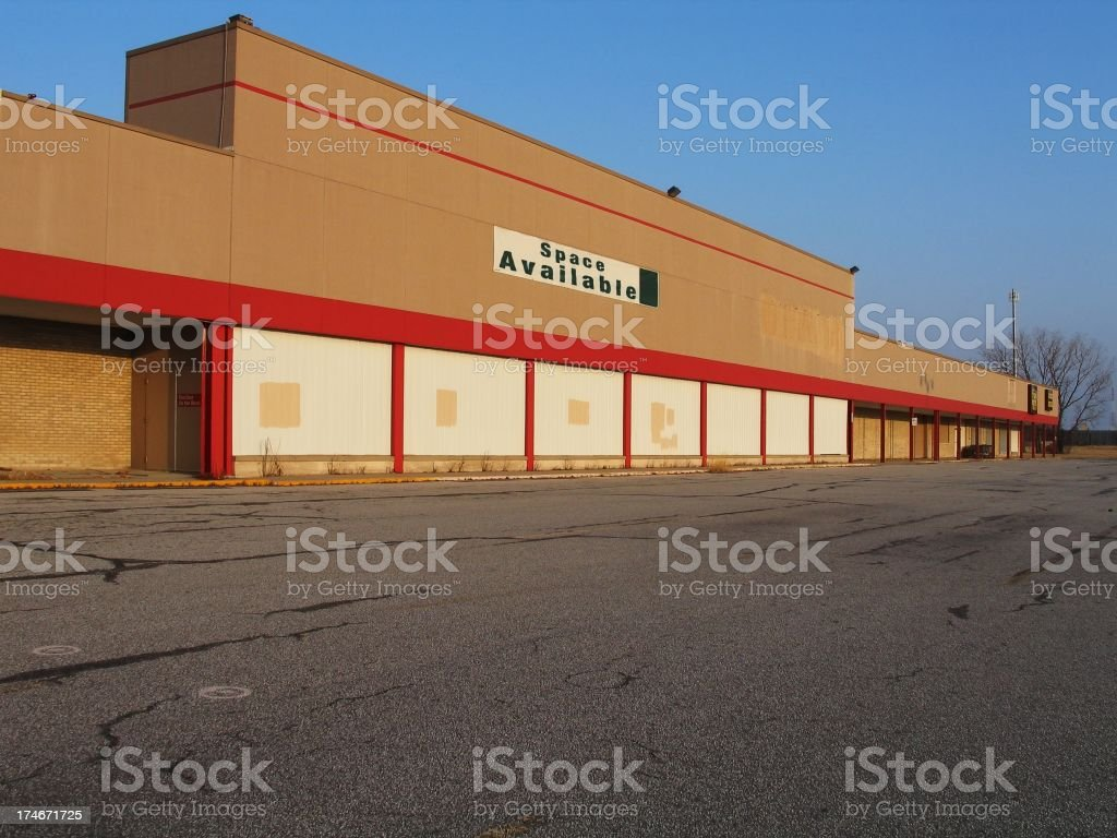 Empty building with a space available sign in front stock photo