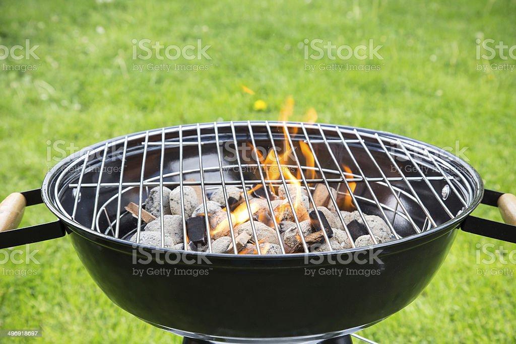 Empty burning grill on garden stock photo