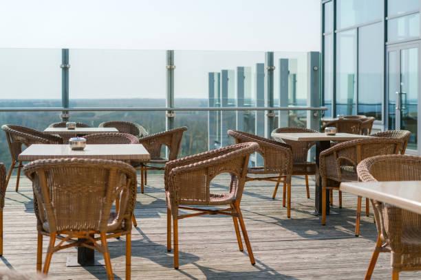 Leeres Café mit Rattanwickelsesseln und Tischen auf der Sommergarten-Terrasse im Freien, Freiraum. Tisch und Stühle im leeren Café. Weidenmöbel rattan-Stühle auf Terrasse – Foto