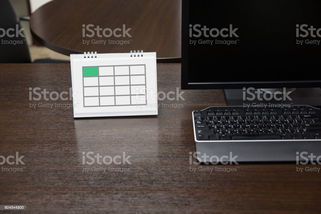 Empty calendar on working table with computer display in modern office stock photo