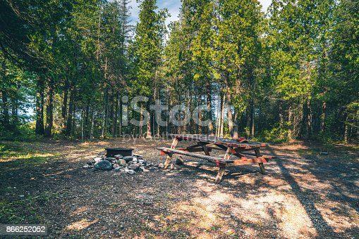 An empty campsite with picnic table and firepit.  Many people consider camping a wonderful escape and have favorite sites that they consider their home away from home.