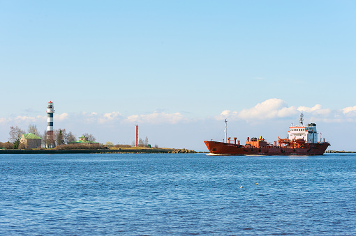 Empty cargo ship entering port of Riga town in Latvia