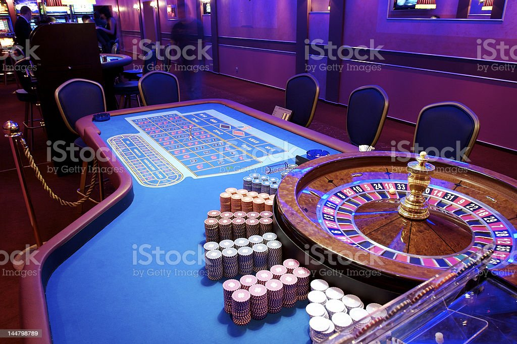 Empty casino roulette table with chairs and chips royalty-free stock photo