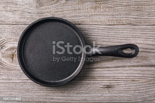Empty cast-iron frying pan on wooden table, top view