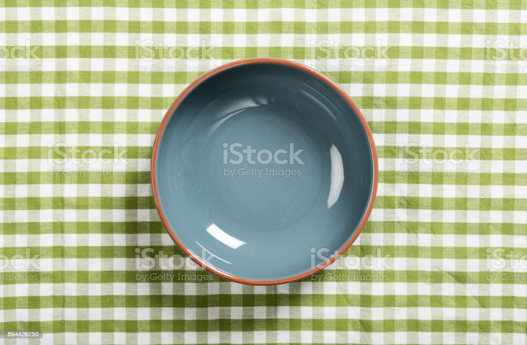 empty ceramic bowl on the table covered with green tablecloth stock photo