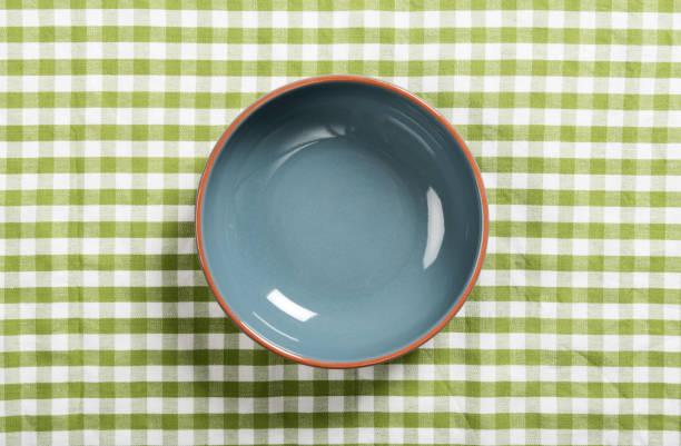 leere Keramikschale auf dem Tisch bedeckt mit grünen Tischdecke – Foto