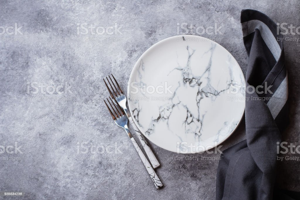 Empty ceramic marble plate, forks and kitchen towel on gray stone concrete table background. Copy space. Menu Recipe Concept stock photo