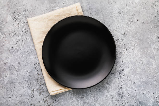 empty ceramic plate in black with a napkin on a gray concrete table, top view - plate stock pictures, royalty-free photos & images