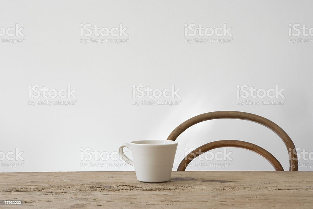 Empty chair and mug on table stock photo