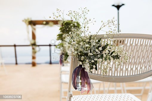 Beautifully decorated folding chair before a wedding. A bouquet of baby's breath is on the chair. An arbor is in the background.