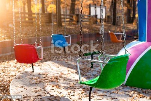 Empty chair multicolored colorful chain swing carousel at old vintage retro entertainment amusement park autumn sunset evening outdoor. Past childhood memories concept. Quarantine closed public area.