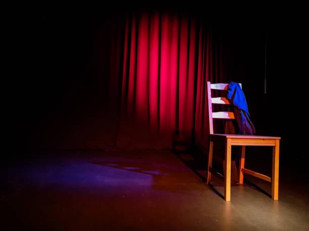 Silla vacía en un escenario de un espectáculo de teatro, concierto o comedia frente a una cortina roja - foto de stock