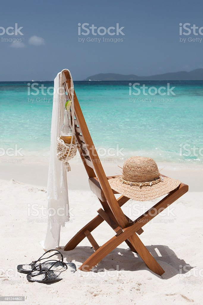 empty chair with hat, cover-up and beer at the beach stock photo