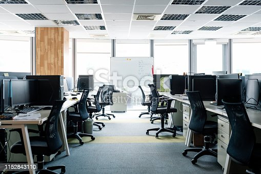 Empty chairs at desks in office. Desktop PCs are on tables. Interior of modern work place with furniture.