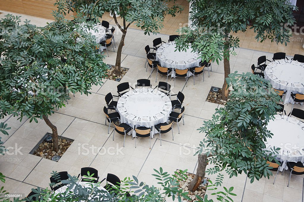 Empty chairs around circular tables in atrium royalty-free stock photo