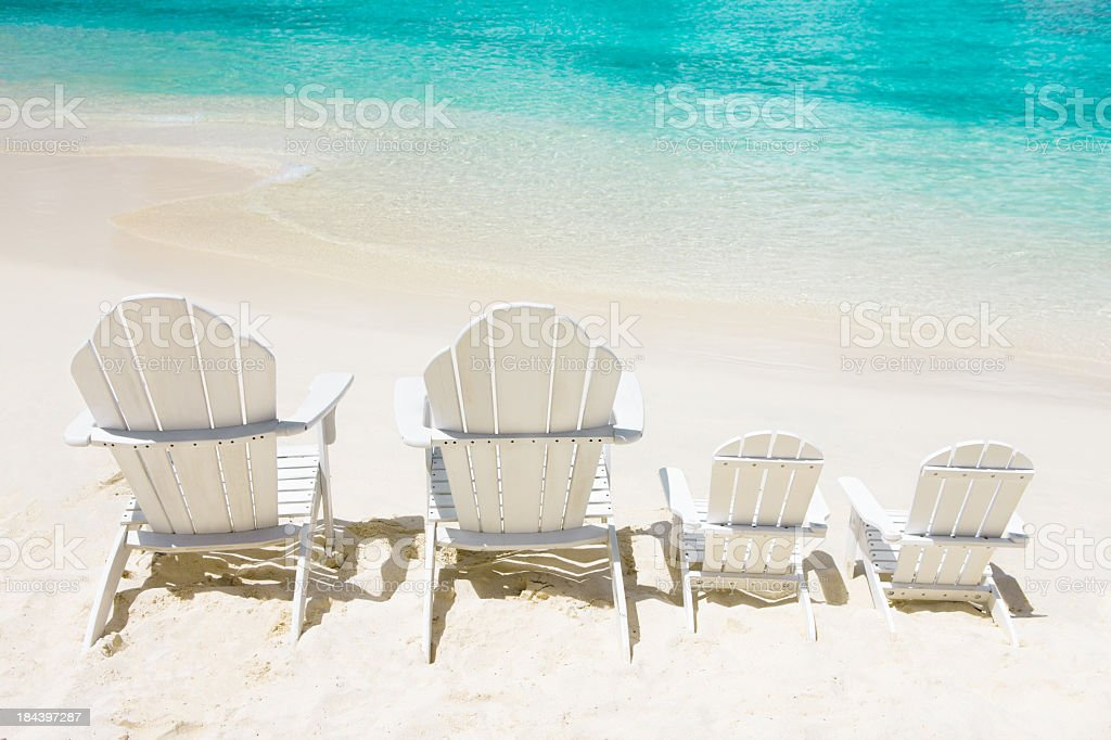 empty chairs for family on vacation at the Caribbean beach stock photo