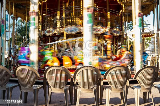 Traditional children's merry-go-round at Boulevard La Croisette in Cannes (France). Empty seats waiting for grandparents and happy children.