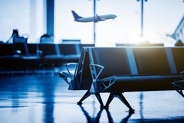 empty chairs , with airplane flying background - airport terminal stock photos and pictures