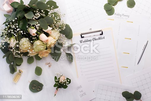 Preparation of wedding. Empty checklist with planner and bouquet of roses on white background
