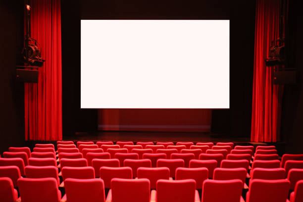 Empty Cinema Room with Red Seats and Blank Screen stock photo