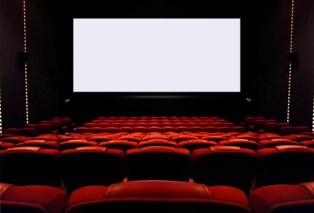 Empty cinema seats with blank white screen stock photo
