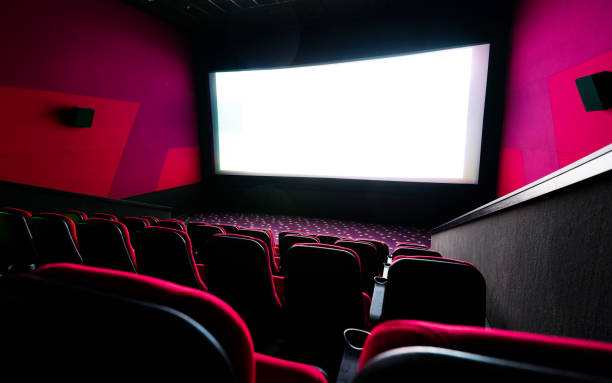 Empty cinema with blank white screen stock photo