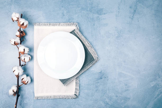 Leere Kreisplatte auf LeinenServietten mit Baumwollblumen auf blau-grauem Hintergrund verziert. – Foto