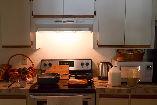 Empty classic American Style kitchen, preparing breakfast and boiling water on the stove at the morning. Black ceramic induction stove with timer on control panel and saucepan on top. Contemporary home style. Bread, milk, eggs, fruits around the desk.