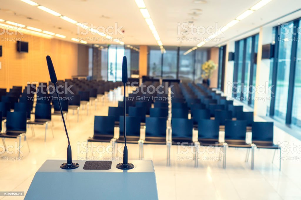 Empty lecture hall with black chairs.