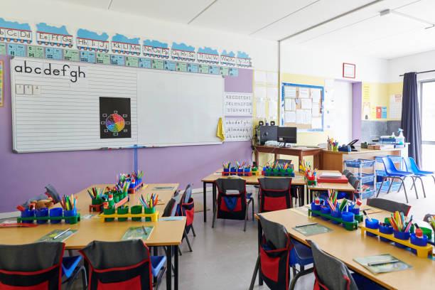 aula vacía en la escuela primaria con pizarra y escritorios - escuela primaria fotografías e imágenes de stock