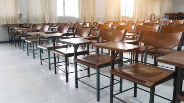 Empty classroom with a lot of chair with no student. Empty classroom with vintage tone wooden chairs. Back to school concept. stock photo