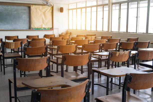 Empty classroom with a lot of wooden chairs stock photo