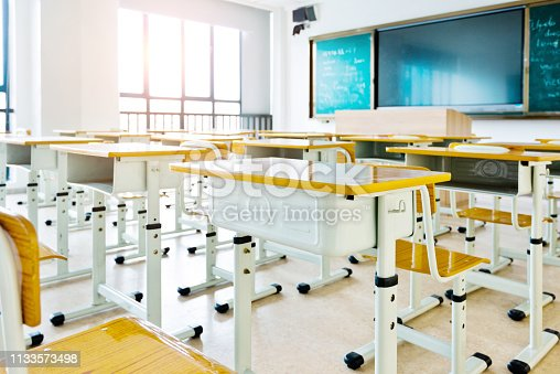 881192038 istock photo Empty classroom with desks and chairs 1133573498