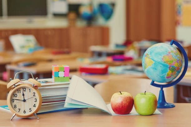 Empty classroom with learning objects, alarm clock and globe. The concept of a break in the lesson. Place for text stock photo