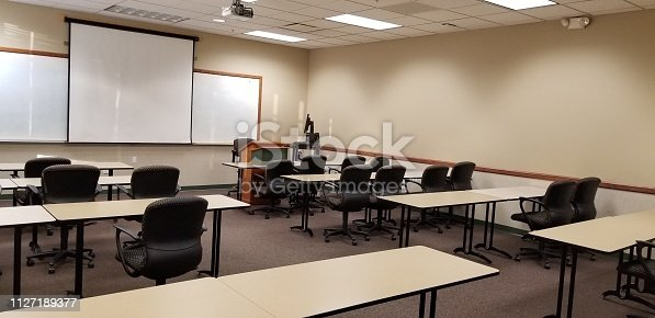 Empty classroom with tables, chairs, podiums, projector and screen view from left back of room