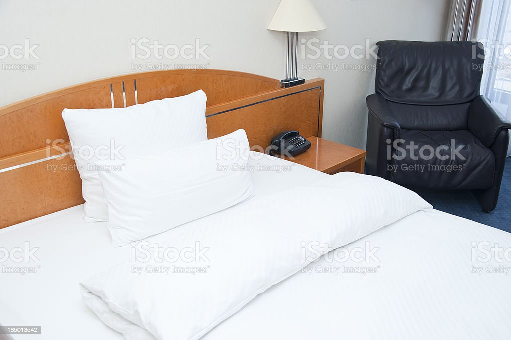 empty clean hotel room with bed and chair stock photo