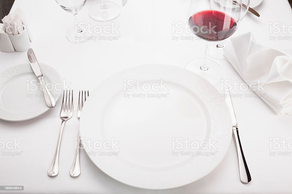 Empty clean white dinner plate with silver knives & forks stock photo