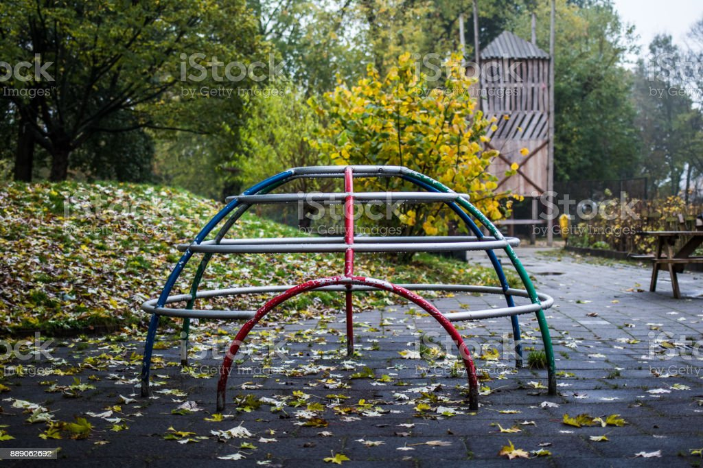 Empty climbing frame without kids at autumn rainy outdoors playground stock photo