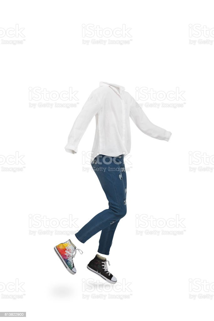 Empty clothes. Child jumping wearing trousers, with shirt and colorful trainers. stock photo