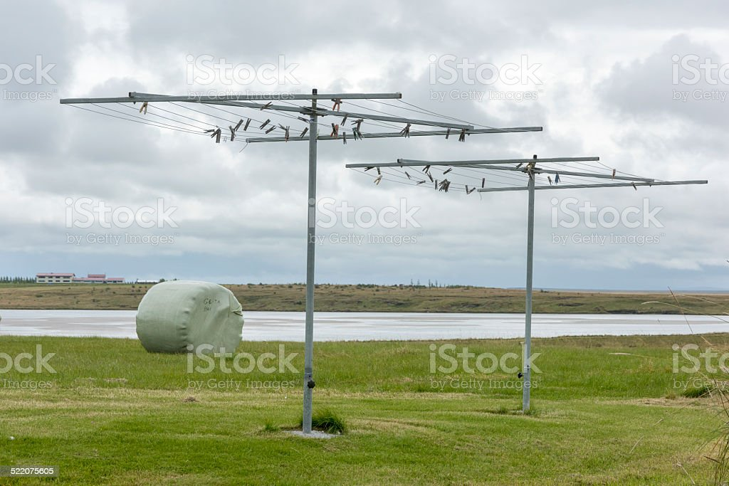 Empty clothesline against cloudy sky and round hay bale stock photo